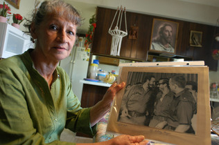Olga Morgan Goodwin is seen holding a photograph of her late husband, William Morgan, right, along with Cuban dictator Fidel Castro, left, at her home in Toledo, Ohio.